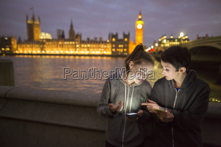 young women illuminated by smartphone opposite