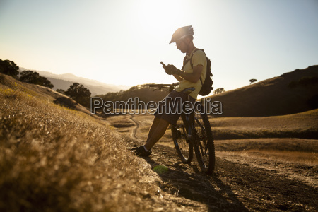 silhouetted young male mountain biker using