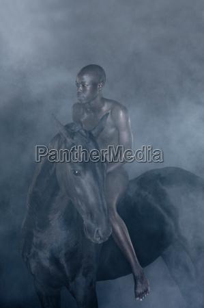 nude man riding black horse