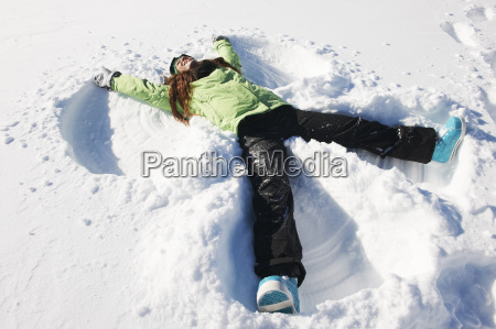 young woman making snow angel kuhtai