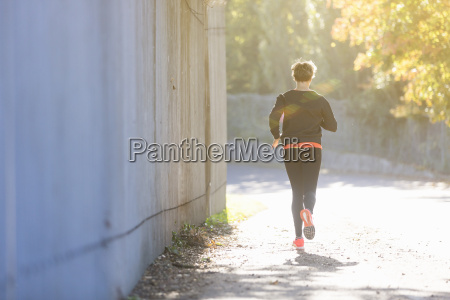 mature woman running outdoors rear view