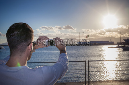 young man taking photograph of sunset