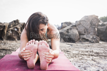 woman holding her feet practicing yoga
