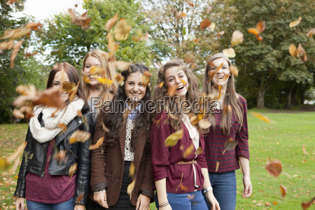 girls playing in autumn leaves in