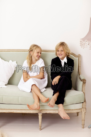 siblings sitting on couch together