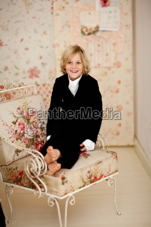 smiling boy sitting in armchair