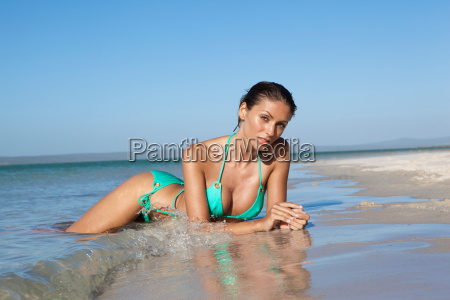 woman crouching in water at beach