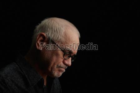frowning older man wearing eyeglasses