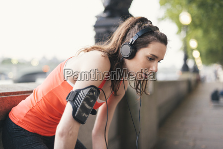 exhausted female runner wearing headphones taking