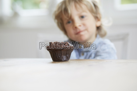 young boy staring at chocolate muffin