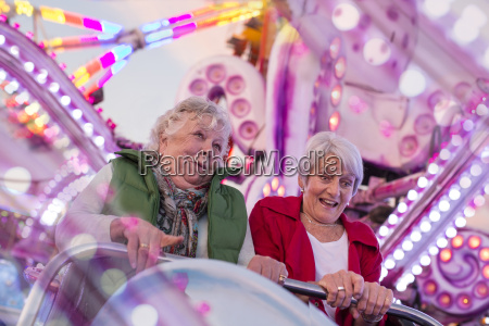 two senior women riding roller coaster
