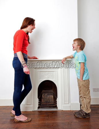 mother and son talking by fireplace