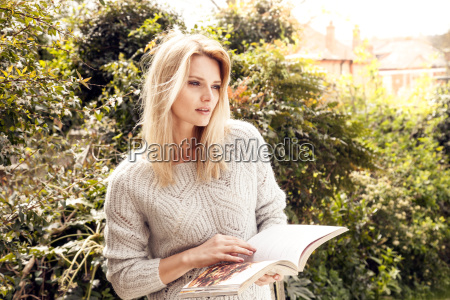 mid adult woman in garden reading