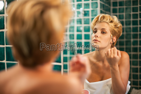 woman applying makeup in bathroom