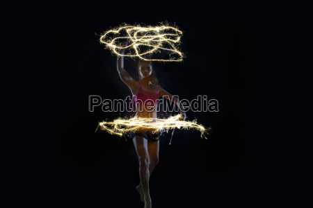 young woman dancing with sparklers