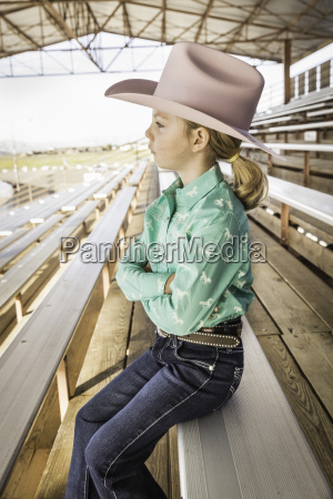 girl wearing cowboy hat on bench
