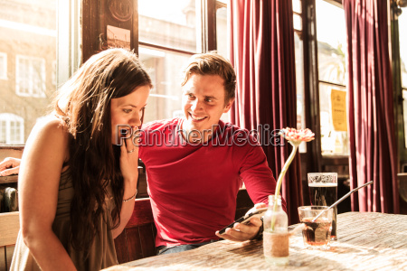 couple using smartphone together hand covering