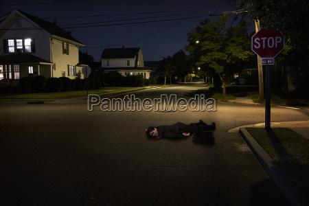 businessman lying on suburban street unconscious