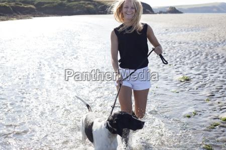 woman walking dog on beach wales