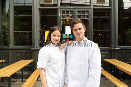 couple in chef uniforms standing outside