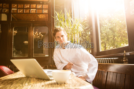 young chef sitting at work looking
