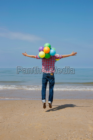 man jumping with balloons on beach