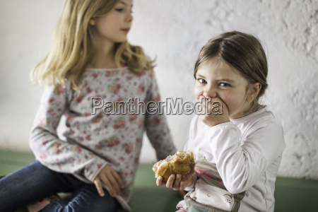 two young girls eating savoury roll