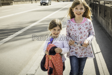 two young girls walking down street