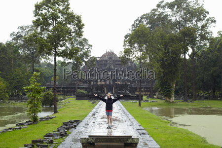 woman standing on walkway to temple