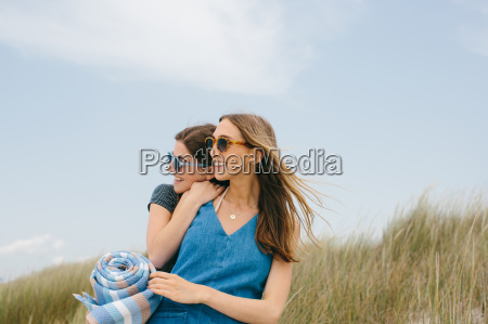 two young female friends carrying picnic