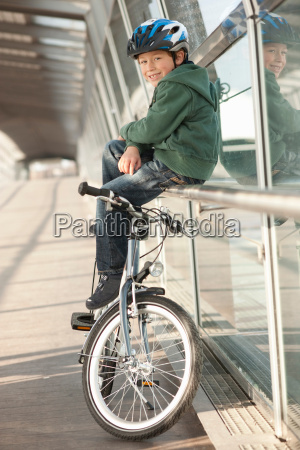 boy sitting by bicycle in city
