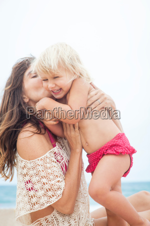 mother playing with child on beach
