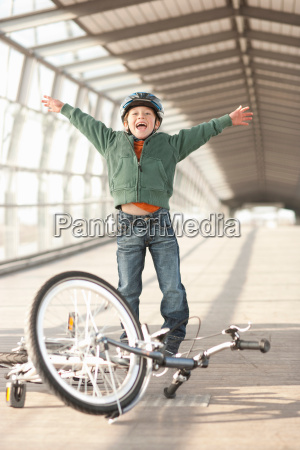 boy cheering with bicycle in tunnel