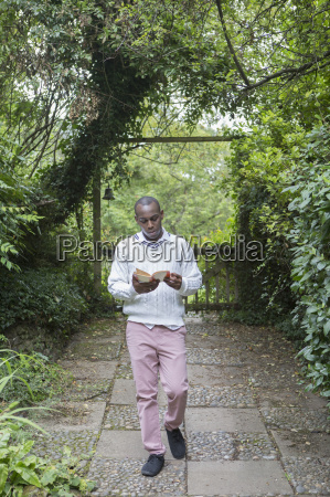 young man reading in garden