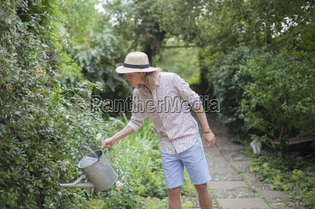 young man watering garden