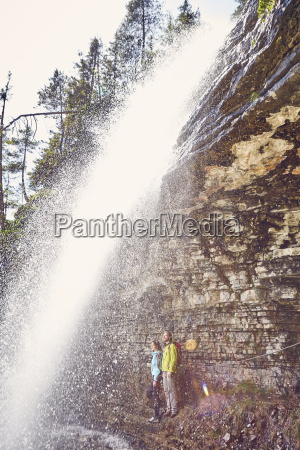 young couple standing underneath waterfall looking