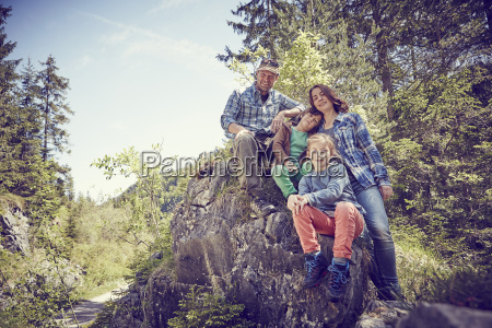 portrait of family sitting on rock