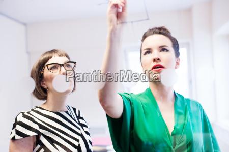 two women brainstorming idea in office
