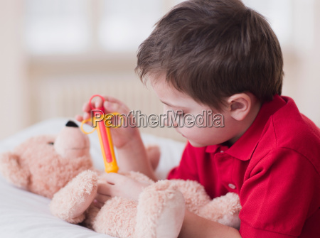 boy playing with toy and teddy