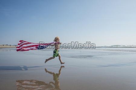 young boy running along beach stars
