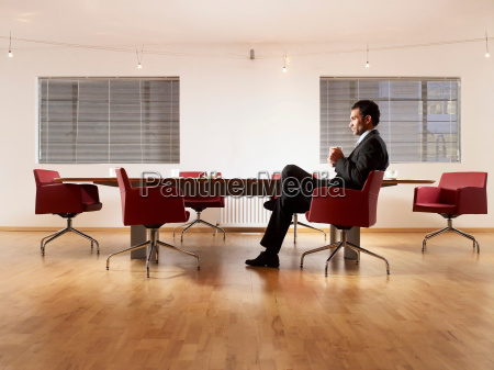 man in suit sitting at boardroom