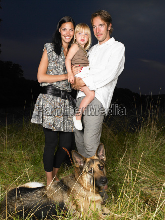 family with dog in a field