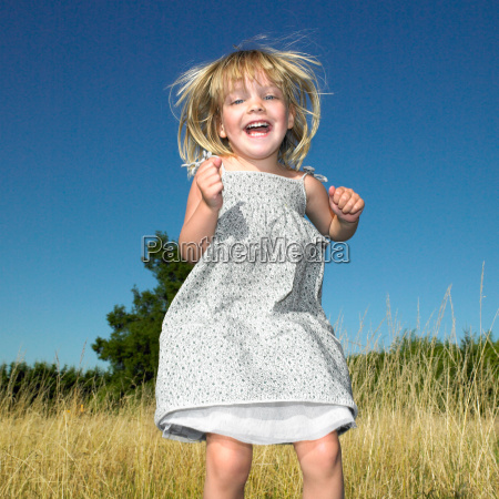 girl jumping in a field