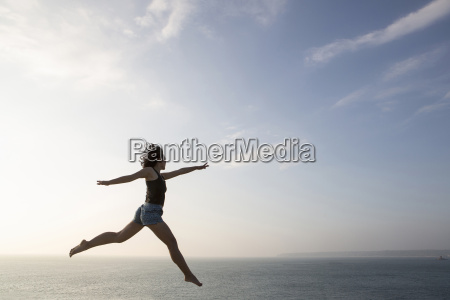 woman jumping against skyline