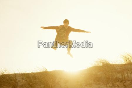 boy jumping for joy on beach