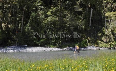 woman wading through river new zealand