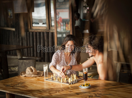 couple playing chess in bar