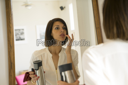 mid adult woman applying lipstick in