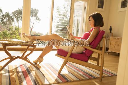 businesswoman reading paperwork in living room