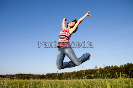 woman jumping on meadow